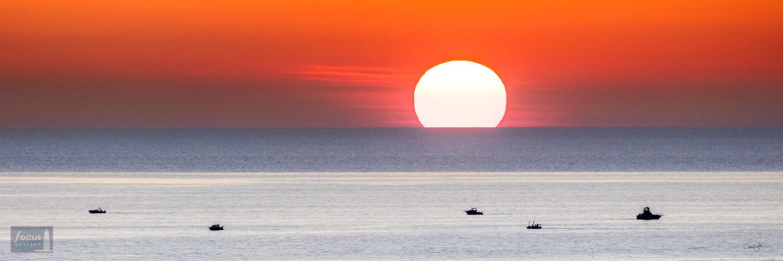 Sunset on Lake Michigan with fishing boats.
