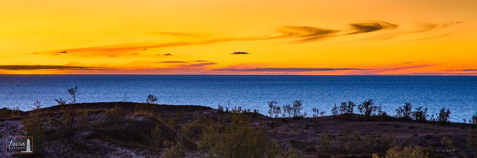 Colorful evening glow over Lake Michigan and bluffs at Sleeping Bear Point.