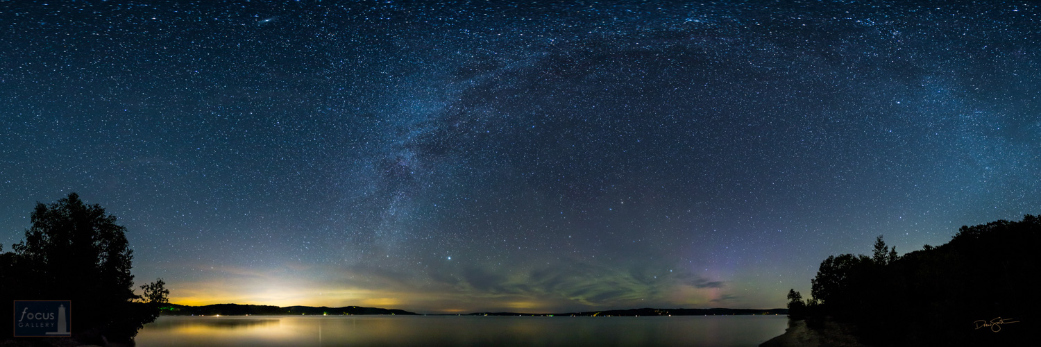 Panoramic view of night sky over Crystal Lake with stars, Milky Way and aurora borealis.