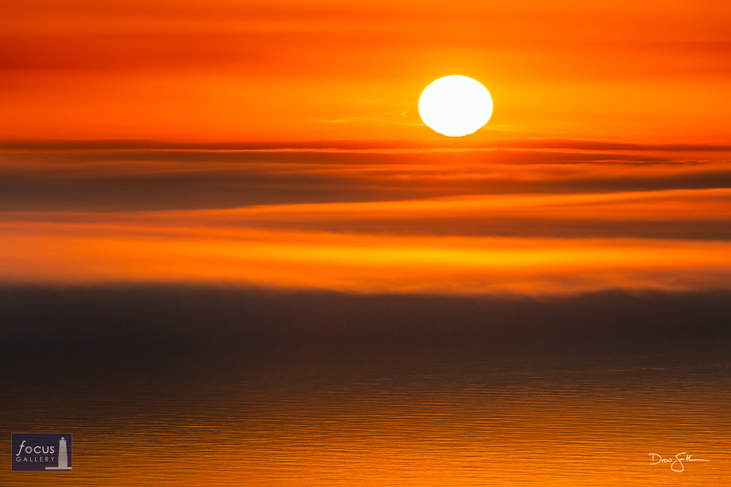 Photo © Drew Smith A layer cake sunset taken from atop the bluffs north of Frankfort.  Frosted in warm orange hues, the sun...