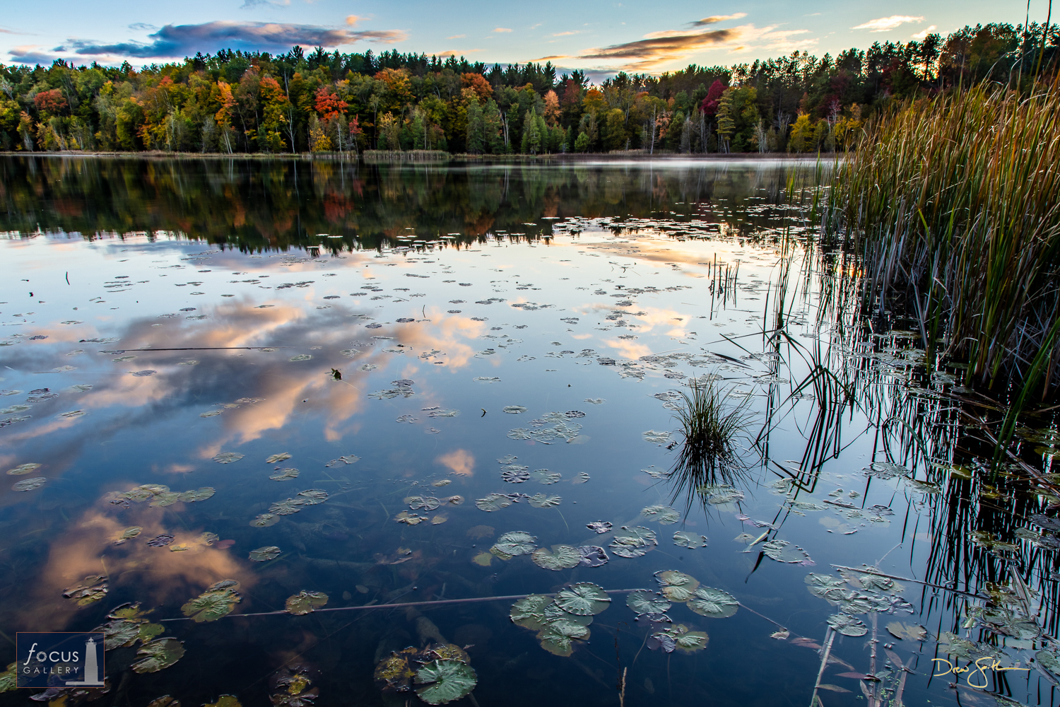 Photo © Drew Smith Blue sky and clouds reflect on the surface of Lower Woodcock Lake as the sun dips below the horizon.   This...
