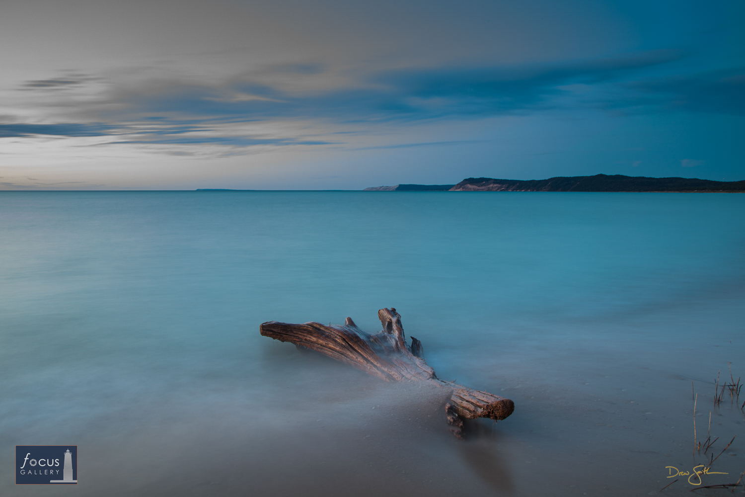Photo © Drew Smith A driftwood log lays partially buried in the sand along Lake Michigan at Platte River Point. I used a long...