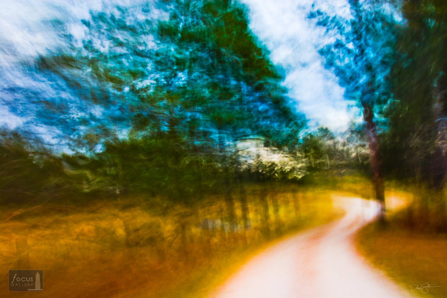 Impressionistic image of a curvy road through trees in the fall.