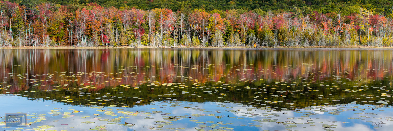 Autumn colors and lily pads reflected on the surface of Tucker Lake in the Sleeping Bear Dunes National Lakeshore.